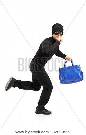 Full length portrait of a thief running with a stolen purse and finger on lips gesturing silence isolated on white background