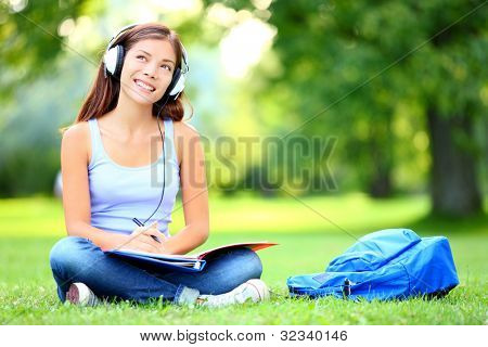 Female student girl outside in park listening to music on headphones while studying. Happy young university student of mixed Asian and Caucasian ethnicity.