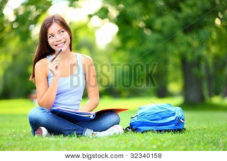Student thinking looking in park Joyful happy asian girl student sitting writing and reading outside on university campus park. Mixed race Chinese Asian / Caucasian female student looking away