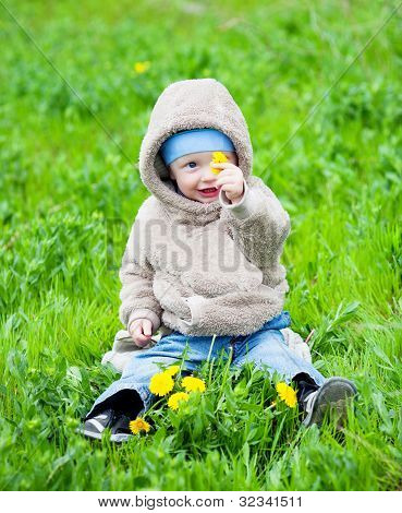 Child Sitting On The Grass