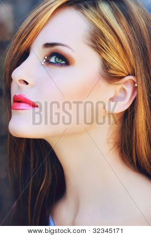 portrait of a beautiful young woman with long brown hair and artistic make-up with pink lips