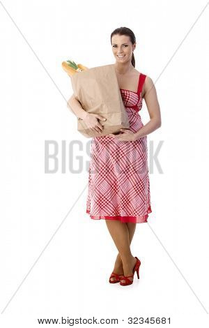 Housewife holding food shopping bag, standing in pretty dress, wearing high heels, full length portrait, cutout on white.