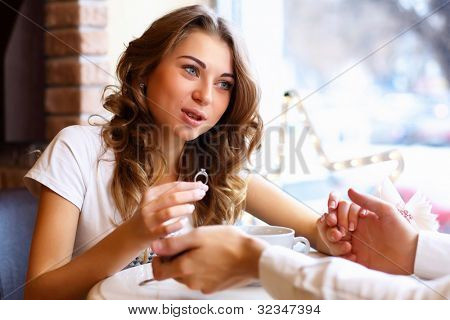 Young couple with a ring during an engagement in a restaurant