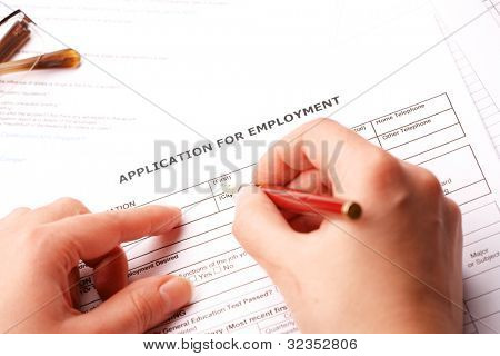 Completing an employment application.Glasses in the background