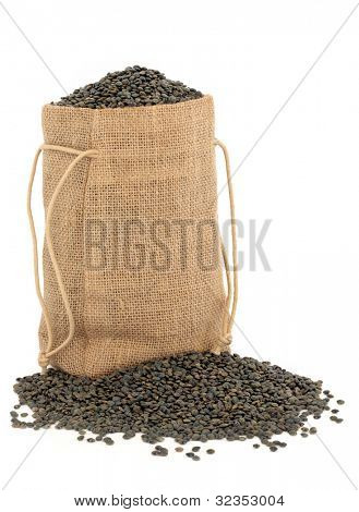 Puy lentils in a hessian sack over white background.