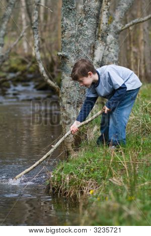 Boy Playing In A Stream