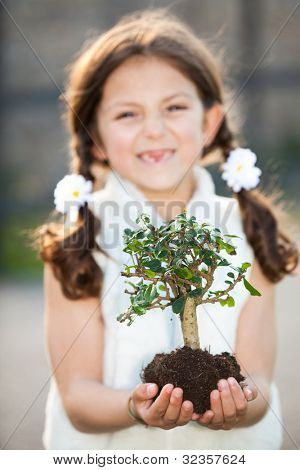 child caring for the environment (focus on tree)
