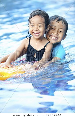 Sibling Having Fun At Swimming Pool