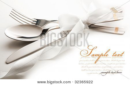cutlery - knife, spoon and fork tied ribbon. isolated on a white background
