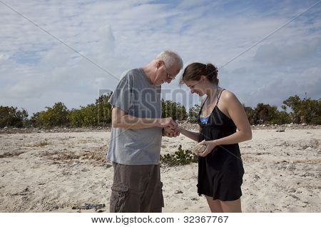 Father and Daughter Examining Shells