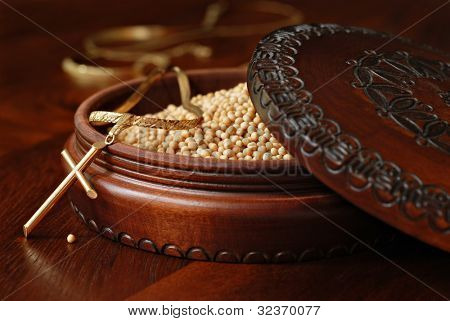 Tiny mustard seeds (symbol of faith) in decorative wooden box with gold cross pendant on wood background.  Macro with shallow dof.  Selective focus on cross with single seed on table.