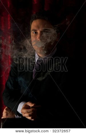 Man In Cigar Smoke In Darkness