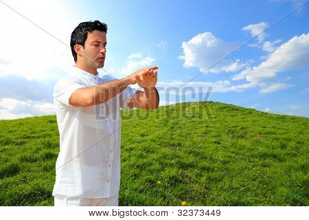 Man in white cloth in the morning meditating at hill background