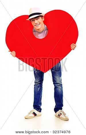 Handsome young man posing with big red heart. Isolated over white background.