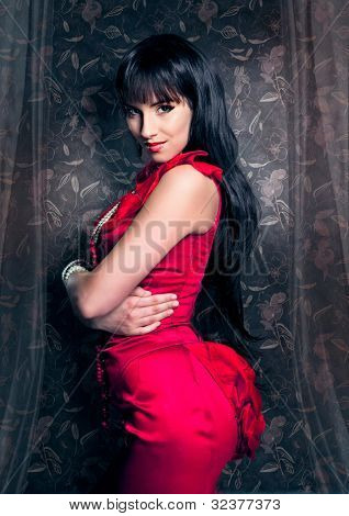 sensual lady with red eveningdress in front of an old wallpaper