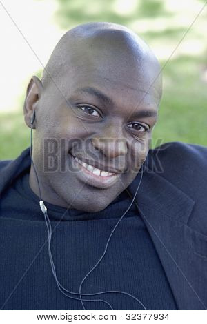 African man smiling with earbuds