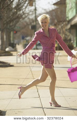 Businesswoman running  on sidewalk