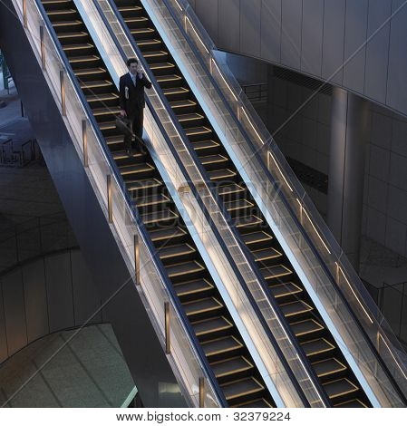 Businessman with briefcase on escalator