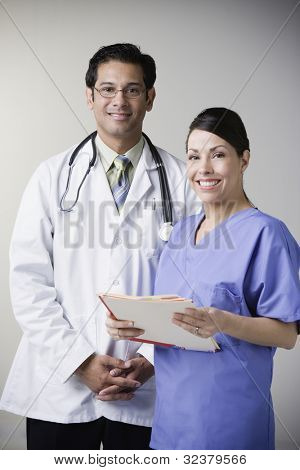 Portrait of Hispanic male doctor and nurse holding file