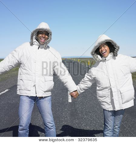 Couple wearing winter jacket holding hands in middle of deserted road