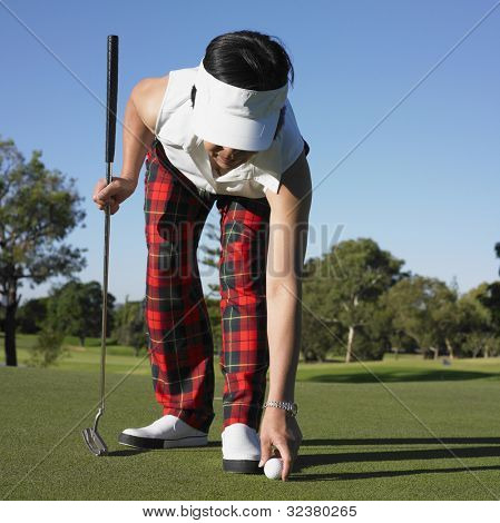 Asian woman placing ball on golf course