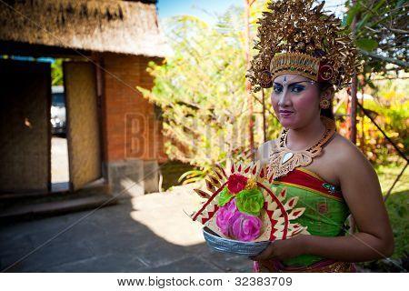 BALI, INDONESIA - 9 de abril: Chica balinesa posando para turistas antes de un clásico nacionales balinés bailar