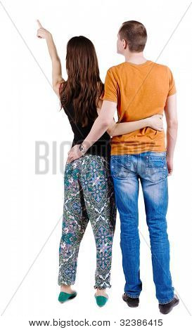 Back view of young couple pointing at wall (woman and man). guy in the jeans and orange T-shirt and the girl in a fashion pants. looking into the distance. Rear view. Isolated over white background.