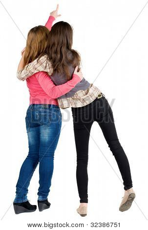 Back view of two young woman pointing at wall . Rear view people collection.  backside view of person. beautiful girl friends  showing gesture.   Isolated over white background.