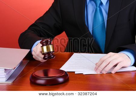 wooden gavel in hand and books on wooden table on red background