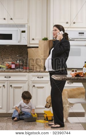 Pregnant  Woman on Mobile Phone with Groceries and Toddler