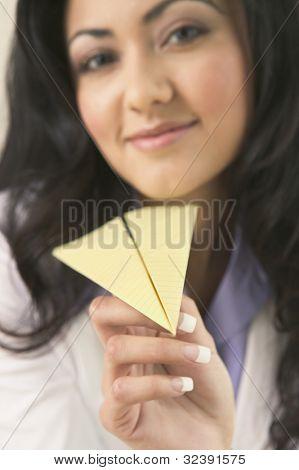 Hispanic woman holding paper airplane