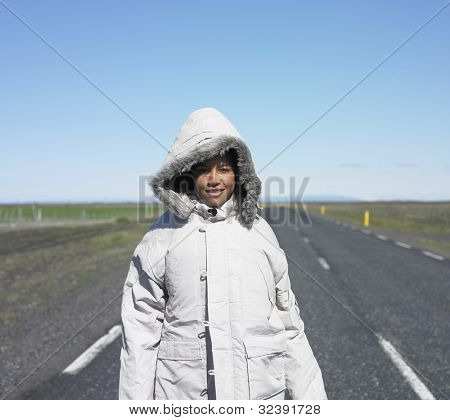 Woman wearing winter jacket standing in middle of deserted road