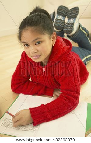 Asian girl doing homework on floor