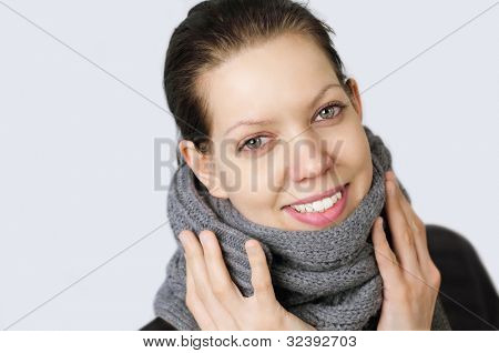 Young woman holding hands on a muffler, because she got a cold, with reddened eyes and nose