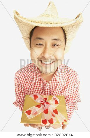 Asian man wearing cowboy hat and holding gift