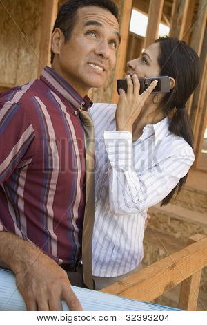 Hispanic couple talking on cell phone in construction site