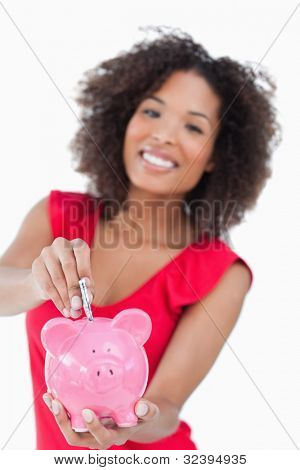 Pink piggy bank being given bank notes against a white background