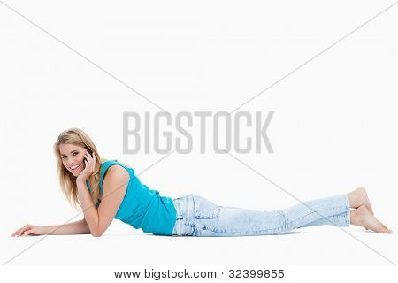 A woman talking on her mobile phone is smiling at the camera against a white background