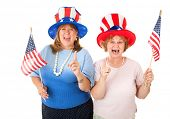Enthusiastic American Tea Party voters in patriotic hats and holding flags.  Isolated on white.