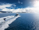 Speedboat with wakeboard rider on open sea. Leasure activities and adrenalin sport concept poster