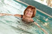 stock photo of swimming  - Mature lady swimming at swimming pool - JPG