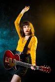 Portrait Of Beautiful Young Hipster Woman With Curly Hair With Red Guitar In Neon Lights. Rock Music poster