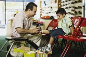 stock photo of comrades  - Young Hispanic boy trying shoes at shoe store - JPG