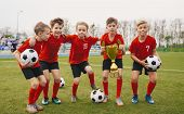 Happy Junior Sports Team. Young Boys In Soccer Team Holding Golden Cup And Soccer Balls. Group Of Ch poster