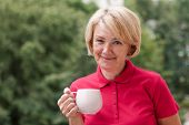 Portrait Of A Happy Elderly Adult Woman Looking At The Camera, Smiling With A Cup Of Tea Or Coffee.  poster