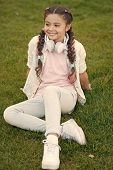 Stylish Happy Child Relax On Green Grass. Little Girl Listen Music. Spring Mood. Mp3 Player. Happy L poster