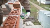 Worker Wipes The Seams Outside The Brick House. The Builder Processes The Brickwork. Construction Ma poster