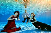 Two Unusual Cute Girls And A Guy Pose And Play Underwater At The Bottom Of The Pool With White Cups  poster
