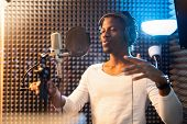 Young African man in white t-shirt and headphones standing by microphone and performing songs in stu poster