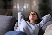 Happy Relaxed Woman Resting Sitting On A Couch At Home In The Night poster